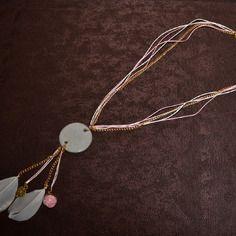 """Sautoir en béton rond """"Doux rêve"""" (par Sésé'Dille).    Vous aimez les couleurs tendres comme le rose, le blanc et le doré ? Ce sautoir apportera une touche de douceur dans vos tenues au quotidien !    Ce collier sautoir est composé d'un pendentif en béton rond, de multi-cordons en coton ciré rose et blanc, d'une chaîne en métal dorée, d'une breloque en métal doré en forme de cœur, de plumes blanches et d'une breloque boule de verre rose."""