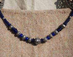 A string of glass beads for Viking age Re-enactment. They are strung on linen thread with silver coloured rings at each end for hanging between Oval (tortoise brooches). There is no clasp so it cannot be worn as a necklace. The beads are replicas of lampwork beads from the viking period, made in the UK and Europe. Each item is completely unique and lovingly composed. Please look at my other listings for different coloured bead strands Thank you for looking! Other accessories not included