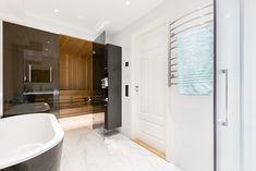 Ett toppmodern badrum i vitt och svart med inslag av turkos mosaik. Duschutrymmet utgörs av en vägg och en dörr i glas. Handfat och toalett är vägghängda och går i färg med det stora svarta badkaret. Bakom en vägg i mörkt glas döljer sig en bastu i två plan med ett modernt bastuaggregat. Alcove, Bathtub, Bathroom, Outdoor, Standing Bath, Washroom, Outdoors, Bathtubs, Bath Tube