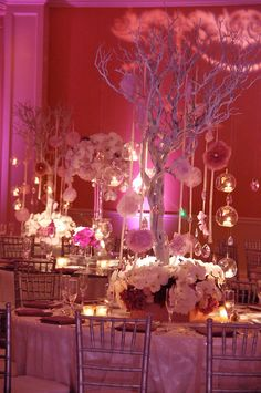 Interesting play with proportion, color and light - centerpieces are different, but all are towering without obstructing view, with a blooming low base; nice combination of spotlighting and hanging candles, reflected by mirrored tabletops...