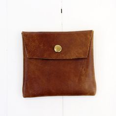 """A handy little snap pouch that can hold cards, money, receipts and other small items.* Soft, 3 oz vintage finish pecan color leather.* Unlined.* Snap button closure.* Bag size: 4.25"""" width X 4"""" heightThis pouch is handmade in California. Since we use genuine leather, the texture of leather naturally varies from piece to piece. Each pouch is unique!Our bags are made to order. Please allow up to 7~10 business days from the date of purchase to be shipped out."""