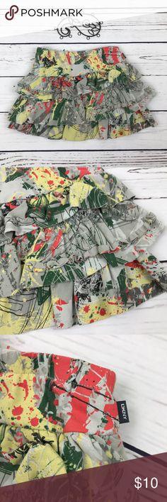 DKNY Girls Paint Splatter Ruffle Skirt Size 24 mo DKNY paint splatter skirt. Asymmetrical ruffles. Has undergarment built in. Size 24 Month. Dkny Bottoms Skirts
