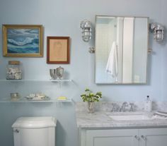 Love the mirror + the use of barn lights as sconces + the glass shelves. And the color. So pretty!