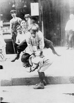 Des enfants jouent à saute-mouton dans une rue de New York, années 1900