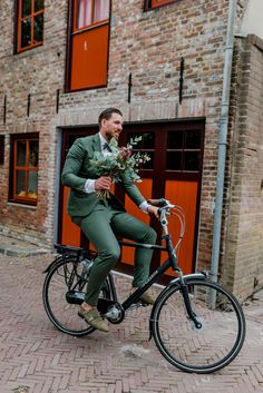 Arrival of a groom on a bicycle with a beautiful field bouquet. A unique green tro . - Arrival of a groom on a bicycle with a beautiful field bouquet. A unique green wedding suit. Rustic Groomsmen Attire, Groom Attire, Groom Dress, Wedding Men, Wedding Suits, Wedding Attire, Wedding Fotografie, Green Wedding Suit, Green Tuxedo
