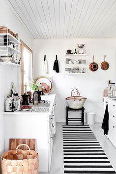 Tältä näyttää Jonnan oman mökin keittiö saaressa. -Se on kompakti pieni tila, johon on valittu vaaleat sävyt. Väritys on valkoista ja harmaata. Mökissä ei ole uunia eikä sähköä, joten ruoanlaitto tapahtuu ulkona kesäkeittiössä. Kahvit keitämme sisällä.