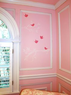 Picture frame moulding in this pretty-in-pink girl's nursery frames a sweet wall decal with hot pink birds and light blush tree branches.