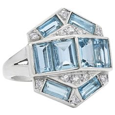 1960's Aquamarine Diamond Cocktail Ring. Baguette aquamarines totaling approximately 2.80 carats are set with a total of approximately 0.25 carats of round diamonds in a 14 karat white gold mounting. The central motif measures approximately 7/8 inch by 3/4 inch wide.