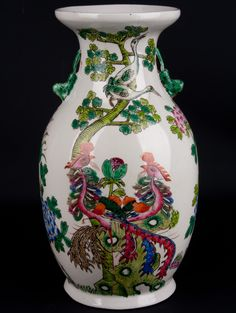 Description A famille rose baluster vase. The flared mouth over neck decorated with cranes on branches and rockwork also supporting a pair of phoenix. The neck also decorated with a pair of squirrel handles. The body painted with lotus leaves and flowers. The tapering body also decorated with birds and rockwork.  Date 20th century  www.collectorstrade.de