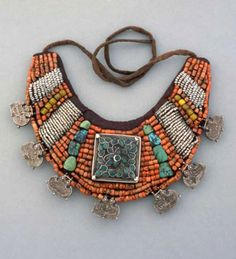 India   Woman's forget (neck ornament); the attached silver pendants have the shape of stylised tiger-claws for the protection of the wearer   Ladakh, early 20th century   coral, seed pearl, amber and turquoise beads and a silver and turquoise ga'u, silver pendants, textile    © From the publication by Truus Daalder 'Ethnic Jewellery & Adornment'   Visit Joost Daalder's facebook page; https://www.facebook.com/pages/ETHNIC-JEWELLERY-AND-ADORNMENT/365830083048