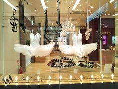 Dance costumes in window display. I like the music staff painted on the glass and lights on the bottom.