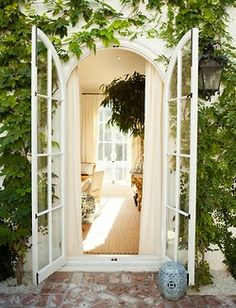 Greenery framing arched door. So lovely.