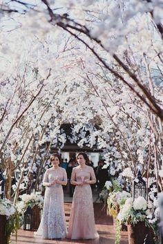 Cherry blossoms as stunning aisle decor for outdoor Bali wedding -- elegant moms walking down the aisle // Wilson and Vania's Sakura Garden Wedding at Alila Villas Uluwatu
