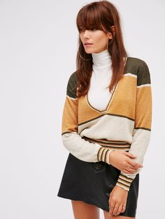 Gold Dust Pullover   Super lightweight pullover with a structured V-neckline and stretchy, ribbed band at the waist. Features metallic fibers strewn throughout with stripe details.
