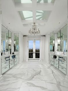 Mirrored vanity cabinets, white Carrara marble floors and a chandelier all add to the sparkle in the master bathroom. cococozy.com
