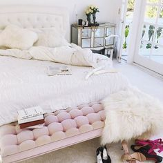 Cozy, cute girl's bedroom with white bedding, faux fur pillows and a dusty pink bench at the foot of the bed | Via Instagram: @stephanielavaggi