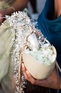The flower girl's basket is replaced with an oversized seashell filled with white petals and decorated with beads.