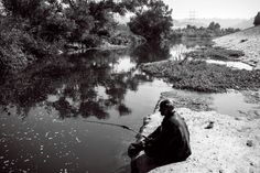 """Samuel (last name not given), an unhoused resident of the LA River, fishes for a meal under a freeway bridge near """"Frogtown,"""" a river-adjacent neighborhood that has seen a steep rise in property values in recent years. Living In La, Property Values, The Neighbourhood, Bridge, Meal, Urban, River, Places, Image"""