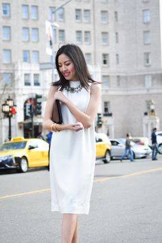 Wear a bold necklace over a simple straight dress with high neckline