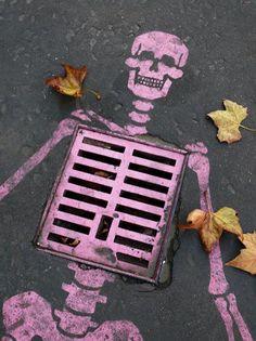 sewer skeleton. pink street art.