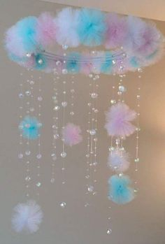 tulle pom poms and crystal beads on a wreath frame make a cute mobile chandelier decor for baby's room or baby shower.