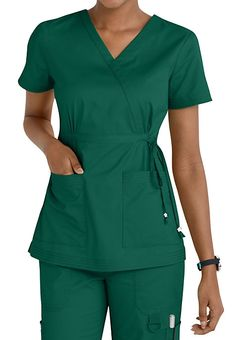 The Koi Katelyn Mock Wrap Top is stylish yet affordable top is highlighted by its flattering mock wrap design with a drawstring waist! Includes roomy pockets for your accessories. Medium center back length 27 Cute Scrubs Uniform, Scrubs Outfit, Green Scrubs, Koi Scrubs, Scrubs Pattern, Stylish Scrubs, Uniform Design, Medical Scrubs, Professional Outfits