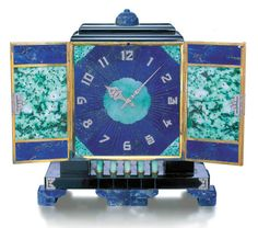 AN ART DECO MULTI-GEM TABLE CLOCK, BY BLACK STARR & FROST.  The front designed as lapis lazuli & carved jadeite doors, enhanced by black onyx Oriental motifs & rose-cut diamond corners, the sides of similar design, opening to reveal a lapis lazuli etched sunray dial with diamond-set Arabic numerals & carved jadeite trim, to the carved lapis lazuli top, with push-piece opening mechanism, supported by jadeite columns to the diamond-trimmed onyx plinth & lapis lazuli  bracket feet, circa 1925