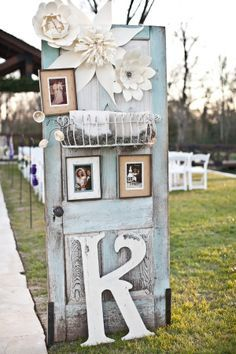 This antiqued vintage turquoise door is the perfect place to display the couple's photos.  Those paper flowers are a perfect addition!  wedding decorations.  doors and wedding decorations.  repurposed doors.  wedding ideas.  outdoor weddings.  antique doors.