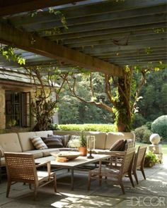 What a beautiful outdoor living room! The simple lines in the furniture are enhanced by the texture of the vines, arbor and the stone work on the house behind the sofa.