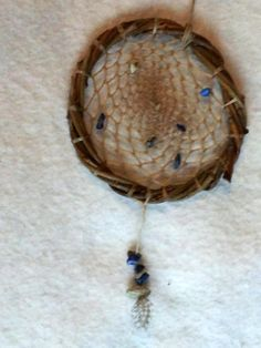 This catcher is made of willow, Sinew and dressed with Blue and White Stones,Guinea Hen feathers