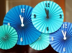 Begin by making assorted accordion circles by cutting strips of cardstock one half the width of desired circle and using scoring blade in your rotary trimmer to score each half inch. Accordion-fold along scored lines and repeat with enough strips adhered together to form a circle. Hot glue at center. Add number stickers Create clock hands Hang with clear thread.