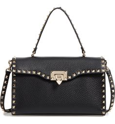Signature studs decorate this structured top-handle shoulder bag from Valentino. Both elegant and edgy.