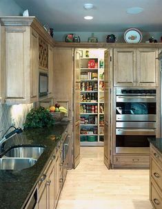 Ubatuba granite countertops stretch across these cabinets that lead into a walk-in pantry.