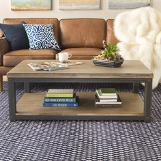 This rustic coffee table features a metal frame with a weather wash grey wood top and bottom shelf. This handsome and sturdy accent table will add an intriguing accent to any space in your home.