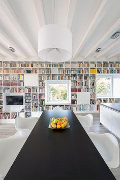Booked Forever , 2013 - FÖLDES & CO. ARCHITECTS LTD. Salle à manger moderne avec un fond une grande Bibliotheque. Table noire entourée de chaises blanches Eames . Vitra