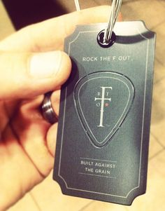 Dig the attitude and concept... Clothing hangtag with break-out guitar pick, hung with real guitar string. Matte black diecut plastic.