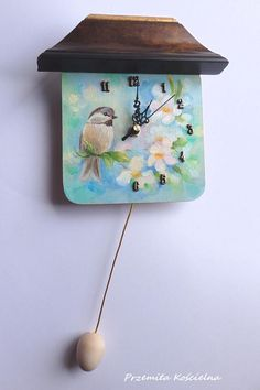 Unique hand painted wall clock  This is funny little wall clock designed and manufactured by artist .  The clock face is an ORIGINAL OIL PAINTING showing a wildlife bird portraits. Title: LITTLE BIRD This funny bird portrait is hand painted with oil paints on the clock face. colors: blue, green, blue teal, brown, gold Painted on wooden panel Painting is signed. size of painted face : 15 x 15 cm = 6 x 6 inch height: 18 cm = 7 inch #clock #painted #funny #wallclock #handmade