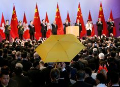 Paul Zimmerman, a district councillor, raises a yellow umbrella as Hong Kong Chief Executive Leung Chun-ying (5th from right) and other officials make a toast to guests at a reception following a flag raising ceremony in Hong Kong commemorating the 65th anniversary of China National Day
