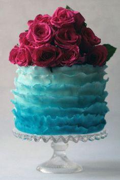 Ruffled cake ombré. Suspiramos com este bolo! O contraste das rosas com o ombré azul ficou de tirar o fôlego. Por incrível que pareça, não ficou tão poluído, porque o cake topper de flores acabou dividindo os holofotes com os babados e o ombré. Apesar de tantos elementos, o resultado foi equilibrado e charmoso.