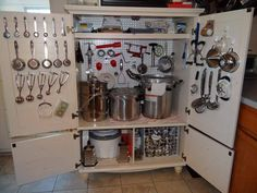 This is a re-purposed TV cabinet for kitchen gadgets, pots & pans.  Would LOVE to have a kitchen cabinet with places to hang the kitchen gadgets near the stove instead of having to rummage through the utensil drawer and NOT finding anything!!!