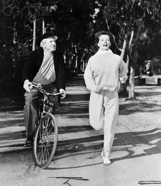 Spencer Tracy rides a bike. Katharine Hepburn runs.  Tags: Spencer Tracy Katherine Hepburn bicycle