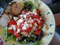 Salad topped w/homegrown tomato & homegrown cucumber salad and grilled pork loin