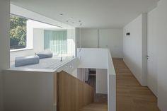 Die prägnante Raumstruktur und Differenzierung der eingesetzten Materialien des Baukörpers setzt sich im 350 qm großen Wohnraum fort. Hier sehen wir den Flur im Obergeschoss inklusive einer eingezogenen Loggia, die den Treppenaufgang mit natürlichem Licht flutet und Blickbezüge zwischen Innen- und Außenraum zulässt. https://www.homify.de/ideenbuecher/31846/haus-mit-verrueckten-fenstern