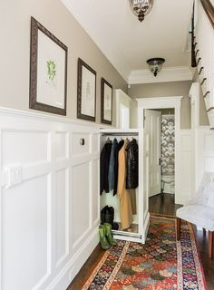 High wainscot paneling add formality and character. A hidden slide-out coat closet built into the wall takes advantage of an unused chase next to the fireplace. At the far end of the hallway, a small powder room was relocated out of the kitchen area to allow privacy within the powder room, as well as create more useable space in the kitchen.