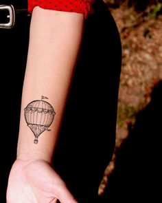 Quite tiny hot air balloon tattooed on a girl's wrist. Cute and inexpensive.