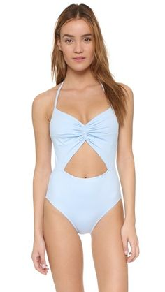 A KORE SWIM maillot with playful cutouts and slim halter straps. Hook-and-eye closure at back. Lined.