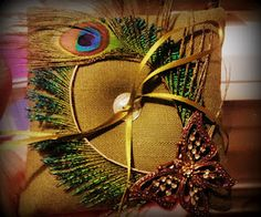 Peacock feather ring cushion with bronze-tone and green gem butterfly.