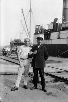 Kaksi miestä, nuori ja vanhempi, poseeraavat kuvaajalle satamassa. Miesten yhdennäköisyyden, ikäeron ja läheisyyttä osoittavan asennon perusteella he saattavat olla isä ja poika. Taustalla seisoo ilmeisesti höyrylaiva Kastelholm. Nuorempi mies saattaa pukeutumisen perusteella olla laivan ravintolatyöntekijä. Kuvaaja: H. Attila, 1930.  VA9810:5523