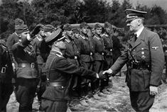 Hitler shakes hands with a very short soldier.