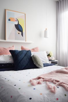 Happy and fun bedroom styling. Polka dot bedding with navy cushions and toucan artwork
